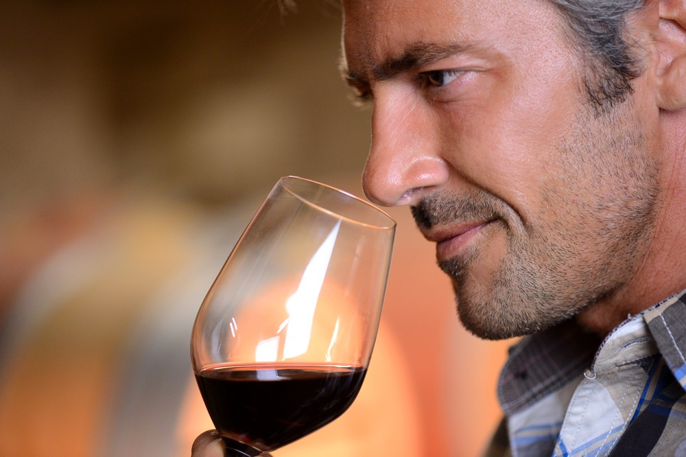 Closeup on winemaker smelling red wine in glass as an event entertainment ideas