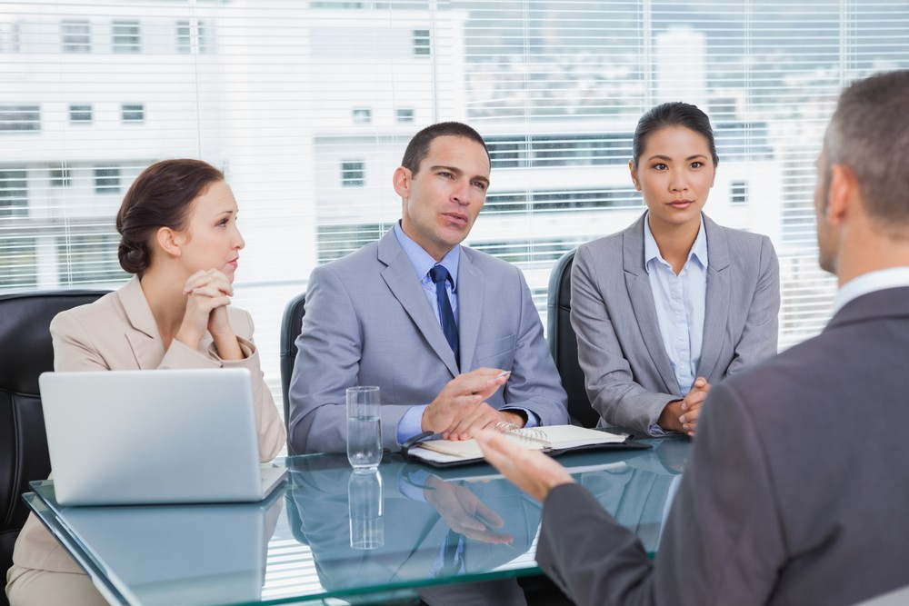 Serious business team interviewing experienced man in bright office